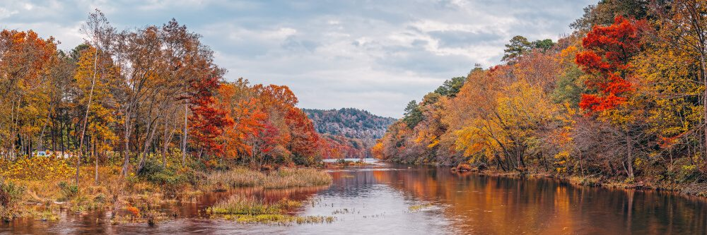 A view overlooking a river and the Oklahoma fall foliage.